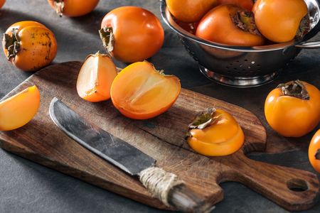sliced and whole orange persimmons on cutting board and in colander