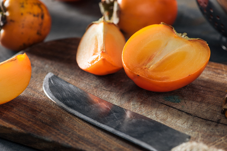 orange and sliced persimmons on cutting board with knife Stock Photo