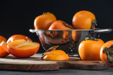 selective focus of orange persimmons on cutting board and in colander