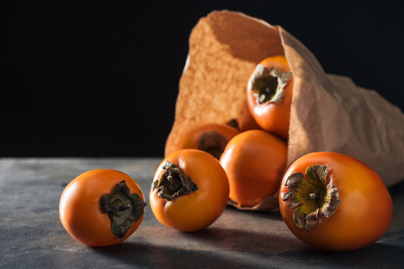 selective focus of orange persimmons in paper packet isolated on black