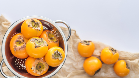 selective focus of persimmons in colander with copy space