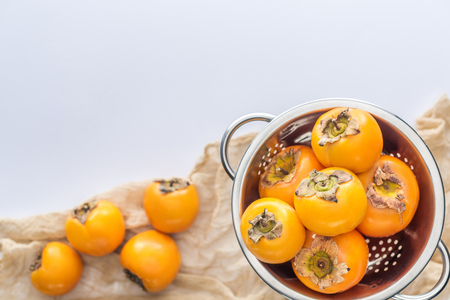 selective focus of persimmons in colander with copy space on white background Stock Photo