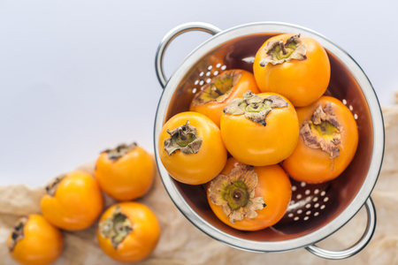 selective focus of ripe whole orange persimmons in colander Stock Photo