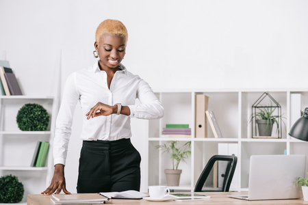 african american businesswoman with short hair looking at watch in modern office