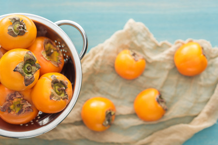 selective focus of whole persimmons in colander on blue background