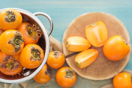 selective focus of ripe orange persimmons in colander and slices on cutting board