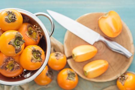 selective focus of orange persimmons in colander and slices on cutting board with knife