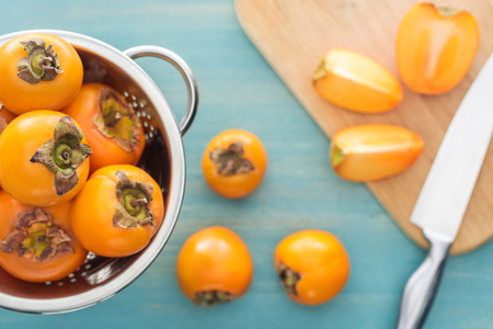selective focus of orange whole persimmons in colander and slices on cutting board Stock Photo