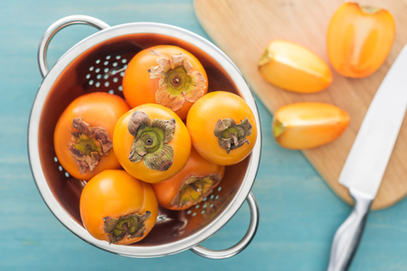 selective focus of persimmons in colander and slices on cutting board with knife