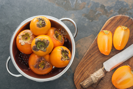 top view of orange persimmons in colander and slices on cutting board with knife Stock Photo