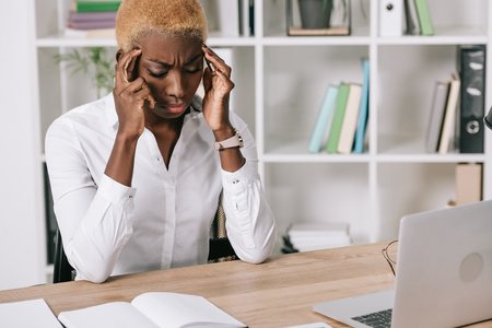 stressed african american businesswoman holding head 写真素材