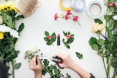 cropped view of female hands cutting chrysanthemums over boutonnieres and lipstick surrounded by flowers on white background Stock Photo