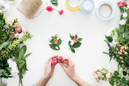 cropped view of female hands holding rose buds over boutonnieres and surrounded by flowers on white background