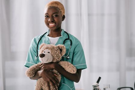 cheerful african american nurse holding teddy bear in light clinic