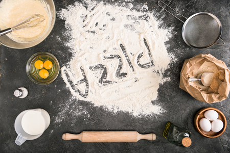 top view of pizza word made of flour with ingredients and cooking utensils on grey background Stock Photo