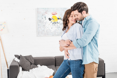 beautiful couple in casual clothes embracing at home