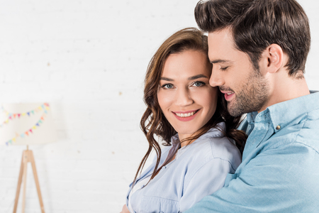 portrait of man embracing smiling woman at home