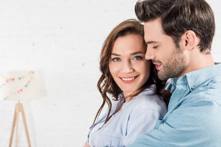 portret van man die glimlachende vrouw thuis omhelst