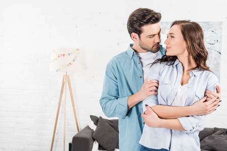 man tenderly embracing attractive woman at home