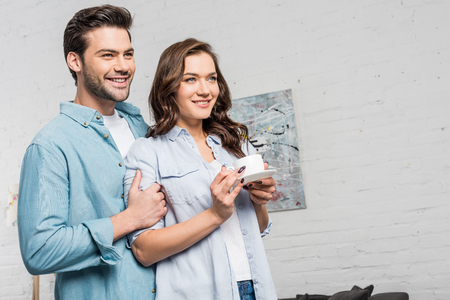 smiling man tenderly embracing beautiful woman holding cup of coffee at home Stock Photo