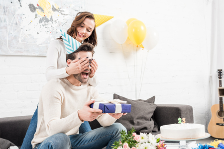 woman surprising excited man with birthday gift in living room
