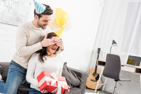 man in party hat closing eyes and making birthday surprise with present for excited woman at home Stock Photo