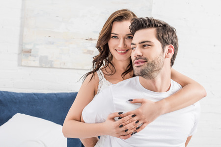 woman tenderly embracing man and looking at camera in bed