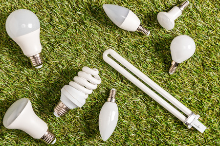 top view of fluorescent lamps on green grass, energy efficiency concept