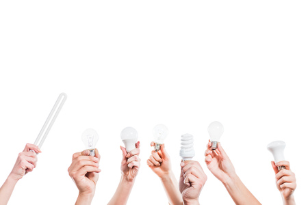 cropped view of people hands holding fluorescent lamps  in hands isolated on white, energy efficiency concept Standard-Bild