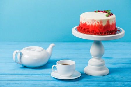 cake decorated with red currants near white cup and tea pot isolated on blue