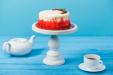 cake decorated with red currants and mint leaves, white cup and tea pot isolated on blue Stock Photo