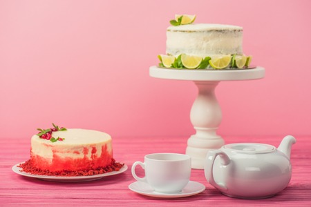 cakes decorated with currants, mint leaves and lime slices near cup and tea pot isolated on pink Stock Photo