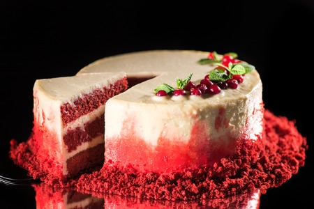 white cake with decorated with mint leaves and red currants near spatula isolated on black