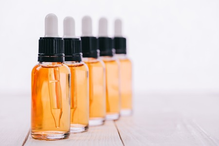 selective focus of cbd oil in bottles with droppers on wooden surface isolated on white