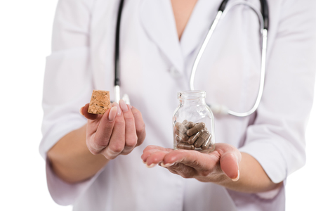 cropped view of female doctor opening up bottle with pills isolated on white Stock Photo