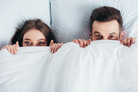 adult couple hiding under blanket in bed