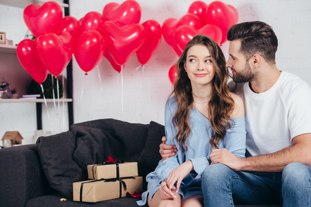 happy man looking at woman in room decorated for st valentine day Stock fotó
