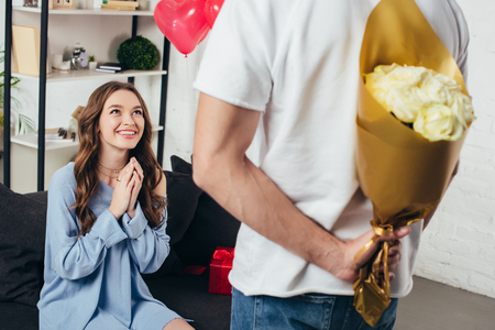 young man holding bouquet of roses behind back while surprised smiling girl sitting with folded hands on sofa Stock fotó