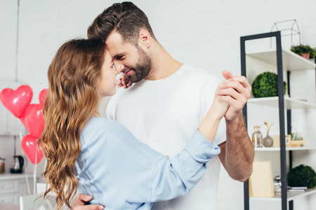selective focus of tenderly smiling couple dancing on st valentine day at home