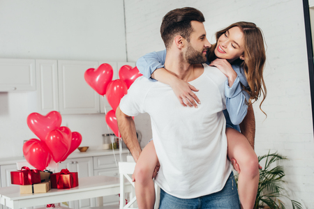 young man giving piggyback ride to smiling girlfriend at home with st valentine day decoration Stok Fotoğraf