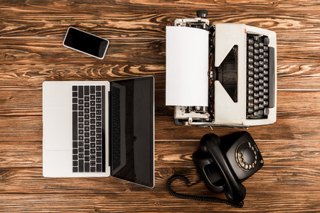 top view of typewriter, laptop, rotary dial telephone and smartphone on wooden table Banque d'images - 117910362