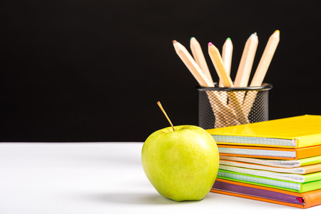 colorful notebooks, pencils and apple isolated on black with copy space