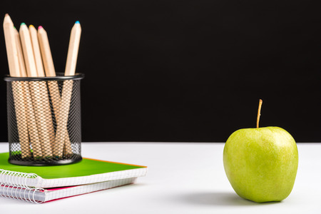 notebooks, pencils and apple isolated on black with copy space