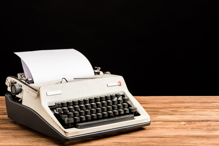 vintage typewriter with paper on wooden table isolated on black