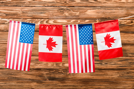 top view of canadian and american flags on wooden background Banco de Imagens