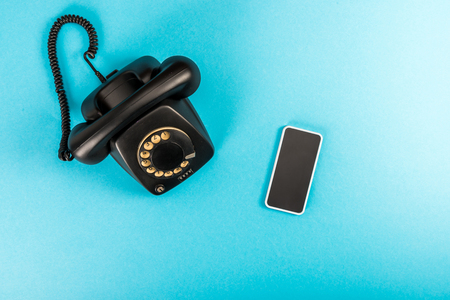 top view of rotary dial telephone and smartphone with copy space on blue background