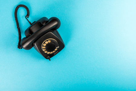top view of black rotary dial telephone isolated on blue with copy space