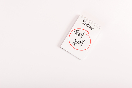 top view of notebook with pay day lettering isolated on white
