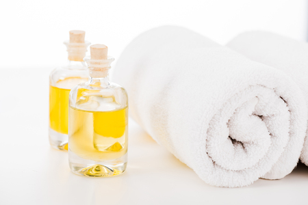 Studio shot of towels and bottles of manicure oil isolated on white
