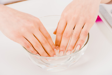Partial view of manicurist with beautiful fingers taking nail bath